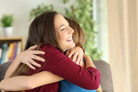 Zwei liebe Freunde oder Schwestern umarmen mit Liebe im Wohnzimmer zu Hause Standard-Bild - 71234183