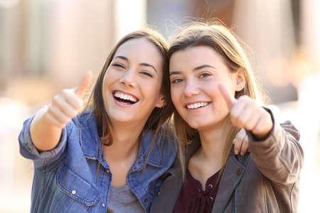 Vista frontal del retrato de dos amigos divertidos con los pulgares arriba y mirando a la cámara en la calle Foto de archivo