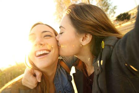 二人の愛情のこもった友人キスをし、バック グラウンドで暖かい光で夕暮れ通りで屋外、selfie を取って