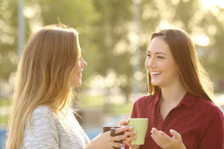 Two happy friends talking holding coffe mug outdoors in a park with a green background at sunset with a warm back light