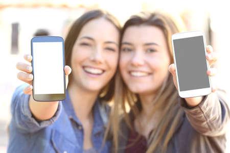 Vista frontal de dos amigos felices mostrando ambas pantallas de los teléfonos inteligentes en blanco en la calle con un fondo borroso