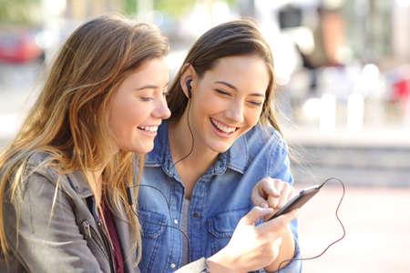 Twee gelukkige vrienden die een telefoon delen om online muziek op lijn in de straat met een stedelijke achtergrond te luisteren Stockfoto