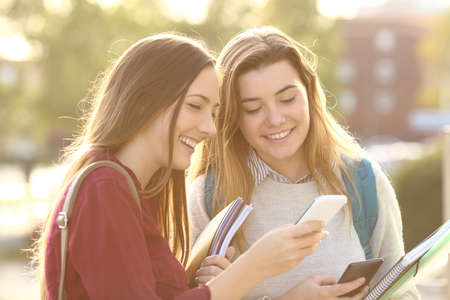 Two beautiful students watching media content on line in a smart phone outdoors in a park or university campus