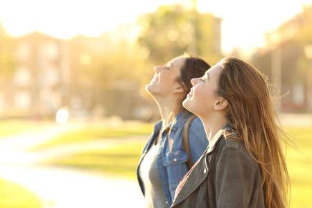 Vista laterale ritratto di due ragazze felici che respirano aria fresca insieme in un parco al tramonto con una luce calda indietro in background