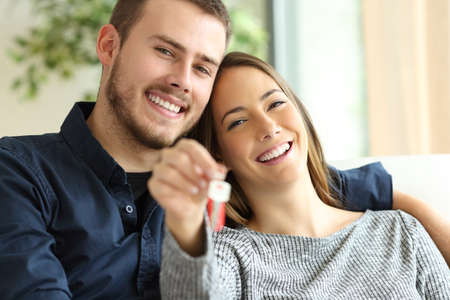 Happy couple of owners showing house keys to the camera sitting on a sofa in the living room at home