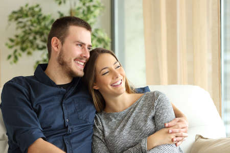 Satisfied couple of householders sitting on a sofa and looking through the window of the living room at home Standard-Bild