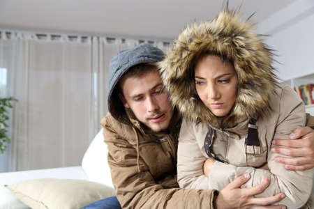Maison froide avec un couple en colère habillée chaleureusement, étreignant assis sur un canapé dans le salon