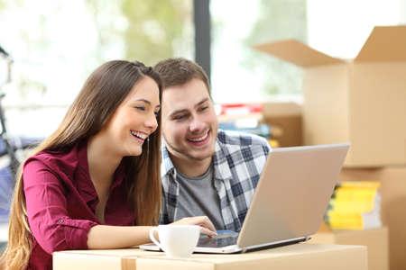 Glückliche Paare, die online mit einem Laptop über einen Karton auf dem Boden sitzen, während der Suche einer Wohnung bezieht,