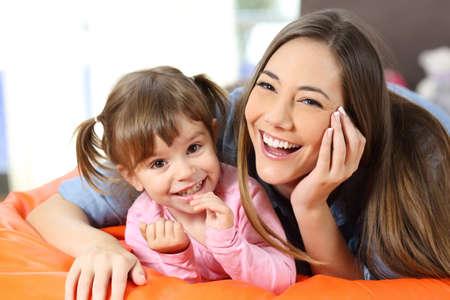Vooraanzichtportret van een gelukkige moeder en een dochter die aan camera in de woonkamer thuis kijken