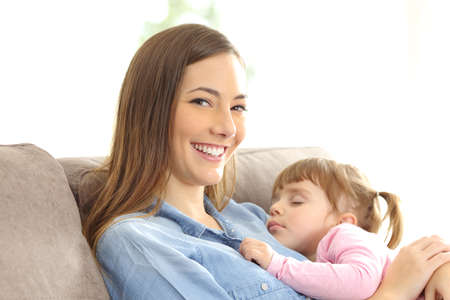 sleep well: Mother looking at you with her daughter sleeping over her chest sitting on a couch at home