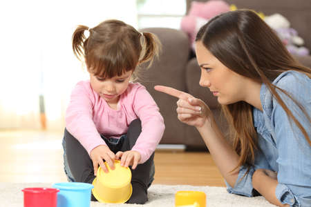 Portrait of a mother scolding to her baby daughter sitting on the floor in the living room at home Foto de archivo