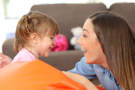 Vista lateral, retrato, de, um, feliz, mãe, e, 2, anos, filha bebê, enfrentando, e, brincando, em, a, sala de estar, casa