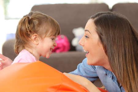 padres hablando con hijos: Vista lateral retrato de una madre feliz y 2 años hija de bebé mirando y bromeando en la sala de estar en casa Foto de archivo