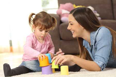 Happy mother and concentrated baby daughter playing with toys together sitting on the floor of the living room at home 版權商用圖片 - 71234126