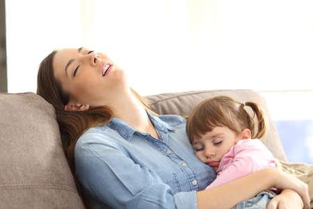 집에서 소파에 앉아 그녀의 잠 들어있는 아기 딸에게 껴안은 피곤 된 어머니
