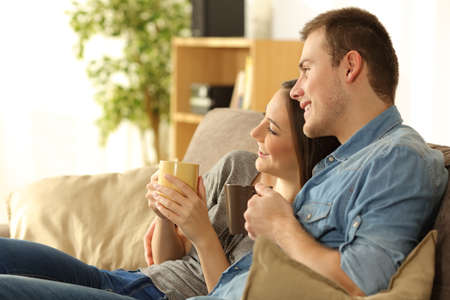 Couple looking away through the window sitting on a comfortable sofa in a homey living room with a warm light in the background