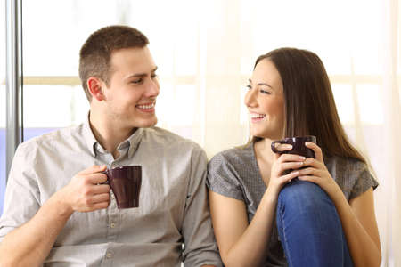Front view of a happy couple talking and drinking coffee sitting on the floor near a window at home Stock Photo