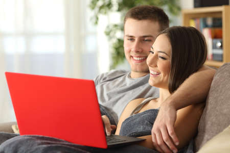 Happy couple browsing internet in a red laptop sitting on a sofa in the living room at home