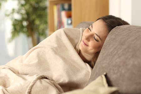 slacker: Relaxed girl sleeping covered with a warmly blanket sitting on a comfortable couch in the living room at home Stock Photo