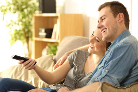 Happy couple watching tv and holding a remote control sitting on a sofa in the living room at home
