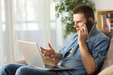Zły człowiek ma problemy na linii z laptopem rozmawia przez telefon komórkowy z obsługą usługi siedzi na kanapie w salonie w domu