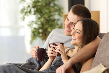 Happy couple relaxing and drinking tea covered with a blanket sitting on a sofa in the living room in a cozy house interior