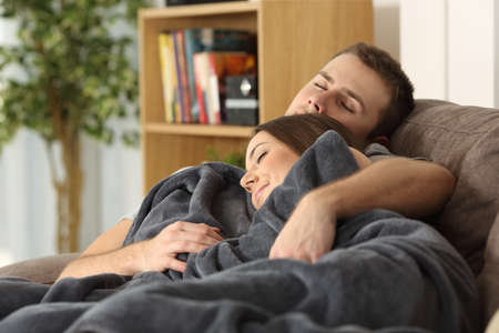 wellness sleepy: Portrait of a relaxed couple embracing and sleeping together on a couch at home lying on a couch in the living room at home Stock Photo