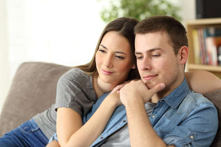 incertitude: Pensive couple thinking sitting on a sofa in the living room at home