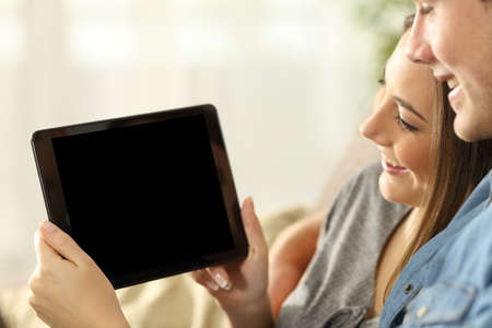 Close up of a happy couple watching media in a tablet and showing the blank screen sitting on a sofa in the living room at home