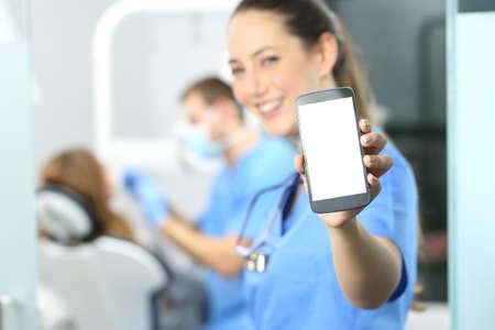 Stomatoloog die telefoonscherm toont en naar u in een tandartsenkantoor interieur ziet met een arts die op de achtergrond werkt