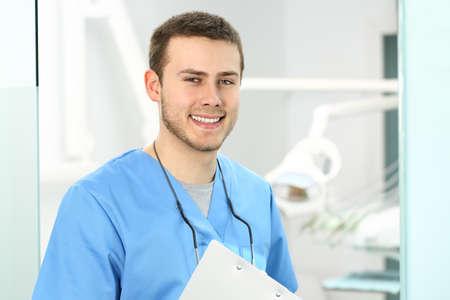 Doctor masculino posando y mirando a usted en una oficina de dentista con equipos médicos en el fondo