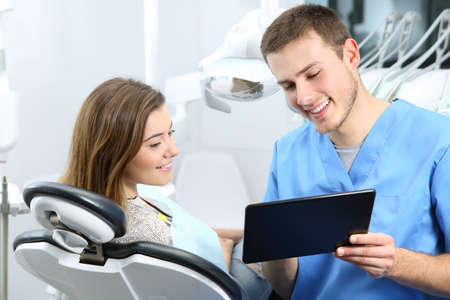 Happy dentist and patient commenting treatments in a tablet application in a consultation with medical equipment in the background