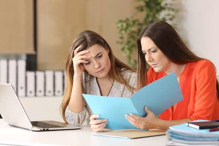 Deux collègues inquiets lisant un rapport ensemble dans un bureau au bureau