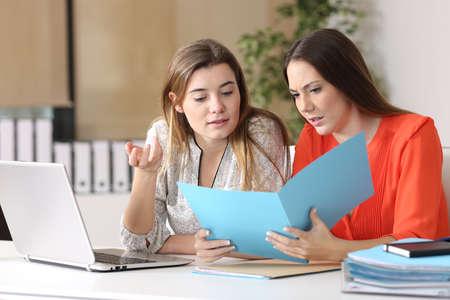 escuchar: Dos compañeros de trabajo graves comentando un informe conjunto en un escritorio en la oficina en un interior Foto de archivo