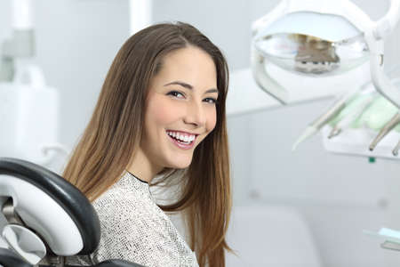 Satisfied dentist patient showing her perfect smile after treatment in a clinic box with medical equipment in the background Stockfoto