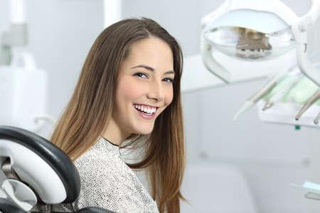 Tevreden tandartspatiënt die haar perfecte glimlach na behandeling in een kliniekdoos toont met medische apparatuur op de achtergrond