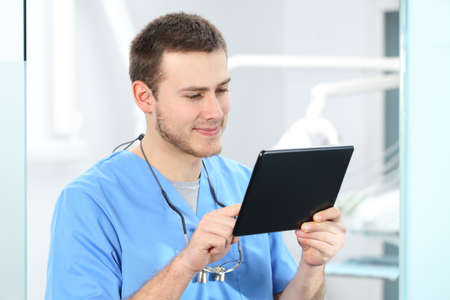 Doctor wearing blue coat working on line with a tablet in a dentist office Stock Photo