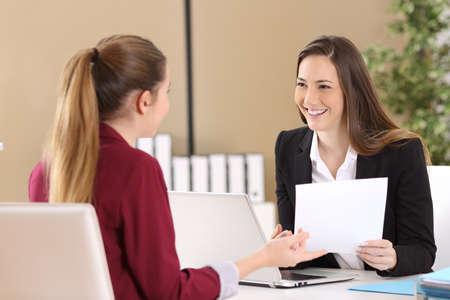 Boss, der an einem Mitarbeiter während eines Vorstellungsgesprächs in einem Schreibtisch im Büro teilnimmt