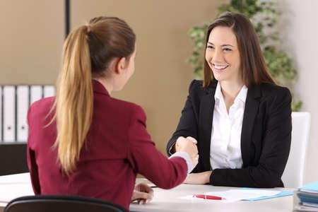 Twee zakenvrouwen dragen pakken handshaking na het ondertekenen van een contract van een goede deal in een kantoor interieur