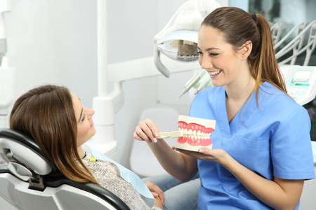 Dentist explaining how to brush teeth correctly to a patient after treatments sitting on a chair in a clinic box with medical equipment in the background