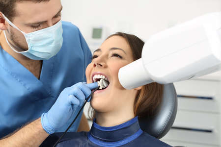 prospection: Dentist taking a teeth radiography to a patient in an office Stock Photo