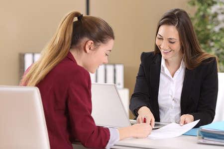 Werknemer of client en interviewer ondertekening van een contract op een desktop in een kantoor interieur
