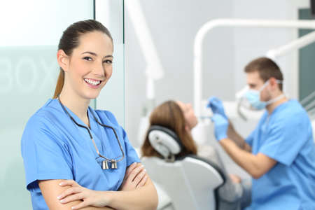 Dentist female with crossed arms wearing blue coat posing and looking at you at consultation with a doctor working with a patient in the background Stockfoto