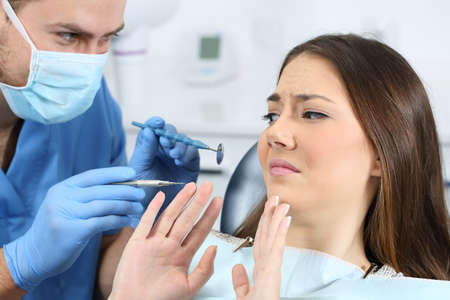 Scared Patienten mit einem Arzt versucht, sie in einer Zahnarztpraxis zu untersuchen