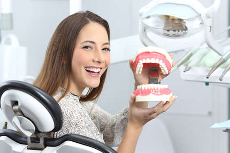 Portrait of a dentist patient smiling with perfect teeth after whitening treatment and holding a plastic denture in a box