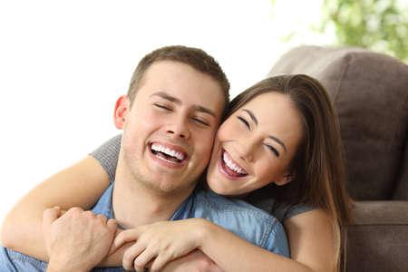 完璧なの白い笑顔ポーズと自宅のソファにカメラ目線で幸せなカップル