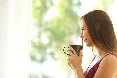 Side view of a single pensive woman standing and relaxing looking through a window at home with a green background outdoors