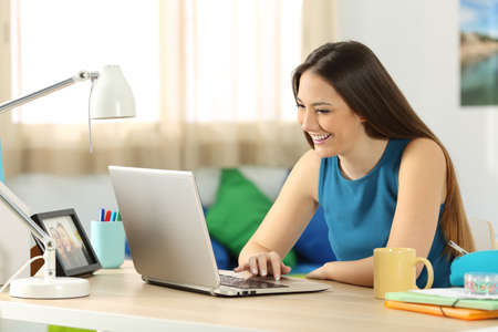 Single student searching content in a laptop sitting on a desk in her room