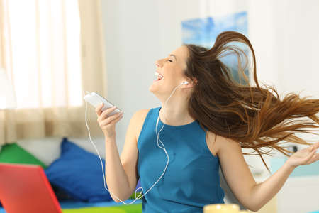 Teen listening to music and dancing holding a smart phone with her hair moving in her room 版權商用圖片