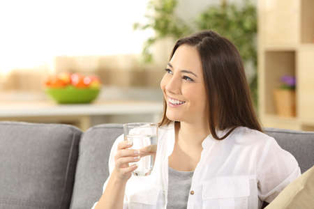 Single woman thinking and holding a glass of water sitting on a couch in the living room at home Stock Photo